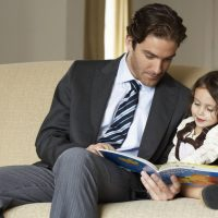 businessman-father-reading-to-daughter-on-sofa