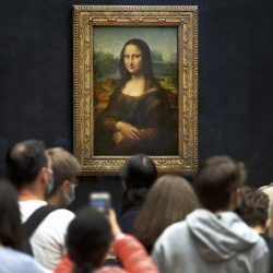 Visitors wearing face masks wait to see the Mona Lisa at the Louvre Museum on Monday. The most visited museum in the world reopened to the public after closing in March.